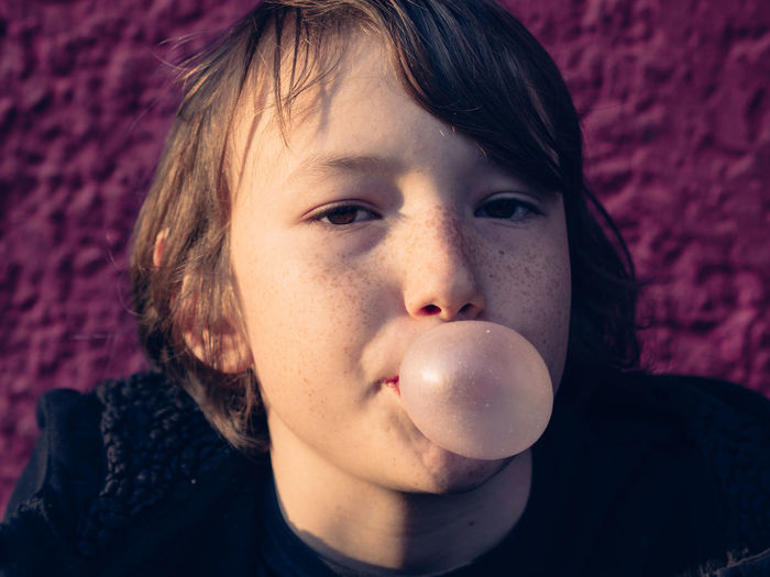Close-up of boy blowing chewing gum
