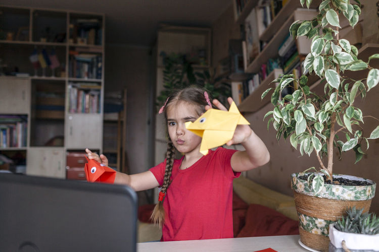 Girl holding origami at home