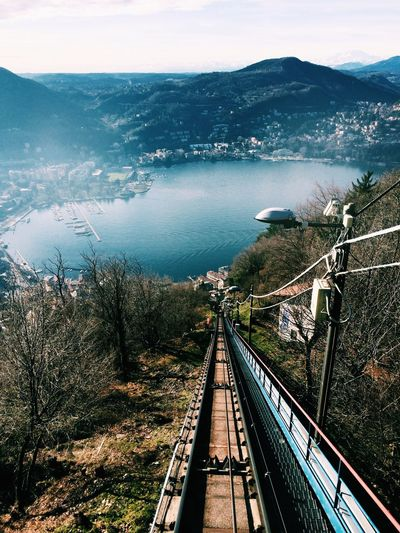 High Angle View Of Railroad Track With Lake And Mountains Against Sky