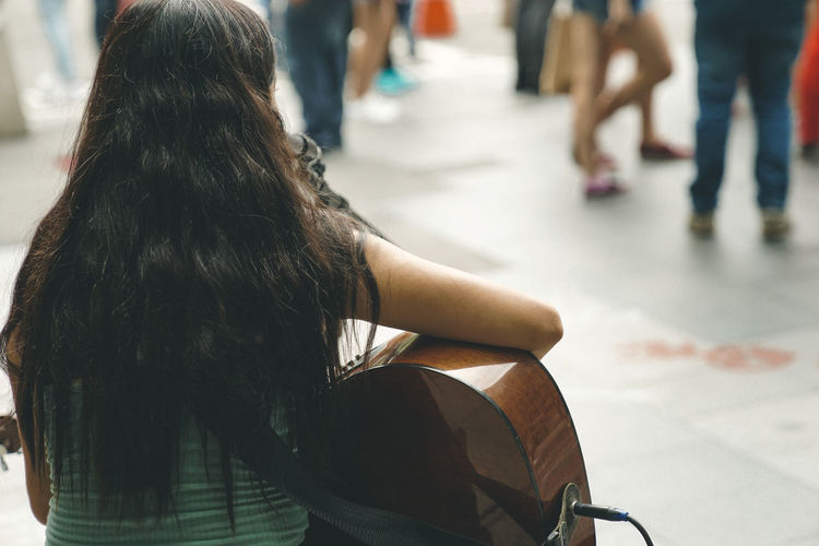 Dreaming Singer  Adult Casual Clothing City Day Focus On Foreground Guitar Hair Hairstyle Human Body Part Human Hair Incidental People Lifestyles Long Hair Musician People Real People Rear View Sitting Street Streetphotography Transportation View From Back Women