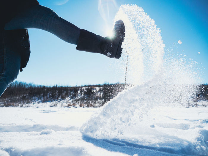 Low section of person on snow against sky