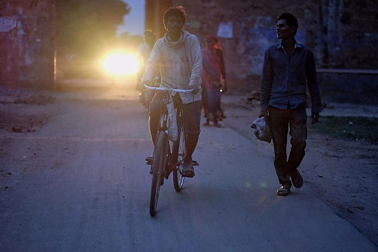 People riding bicycle on street at night