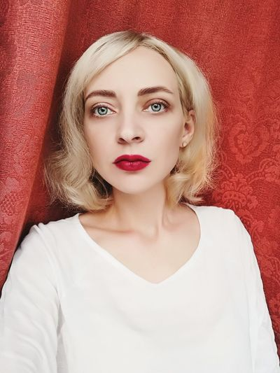 Portrait of beautiful woman against curtain at home