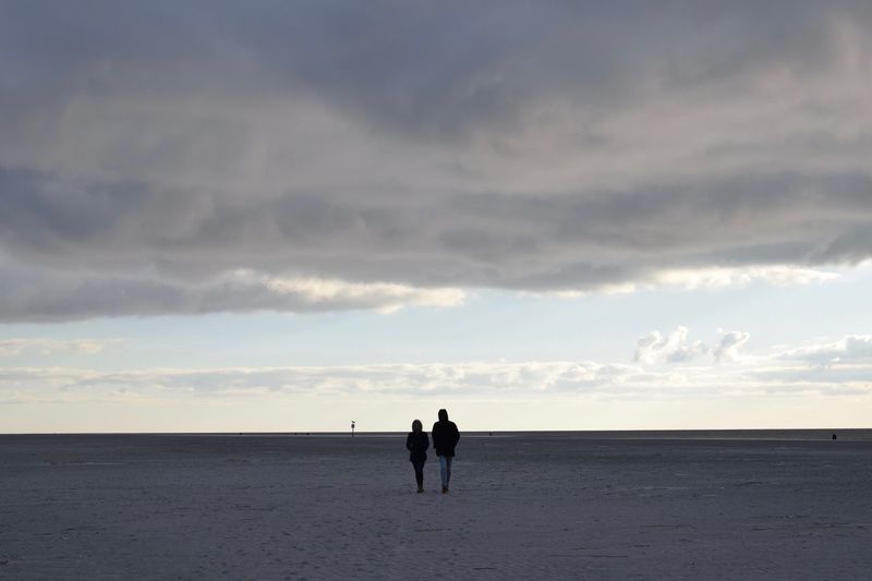 Rear View Of Friends Walking At Beach Against Cloudy Sky