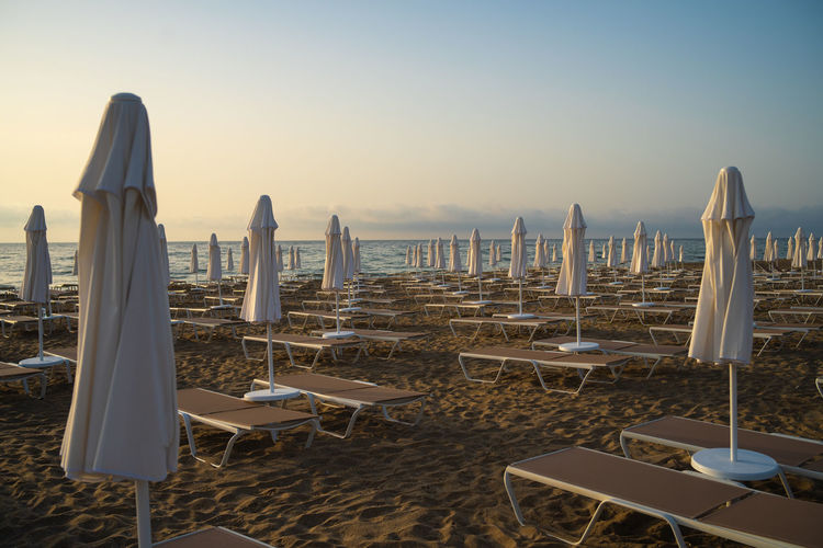 Deck chairs and tables on beach against clear sky