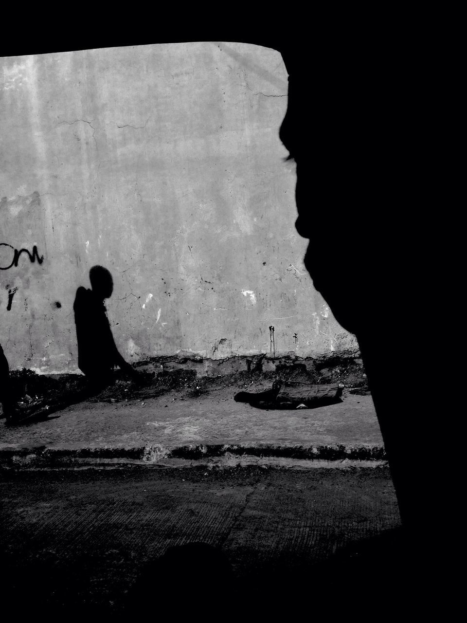 Cropped Image Of Man Looking At Shadow On Wall