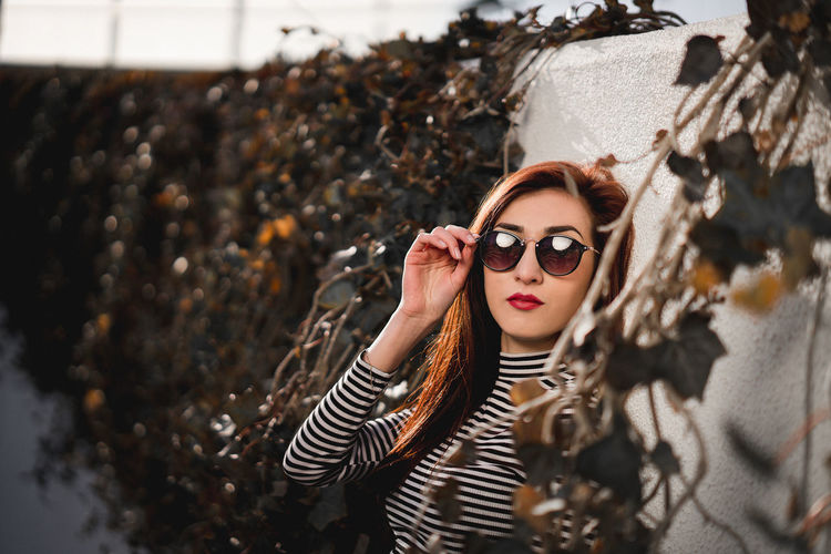 Portrait of young woman wearing sunglasses while standing by wall