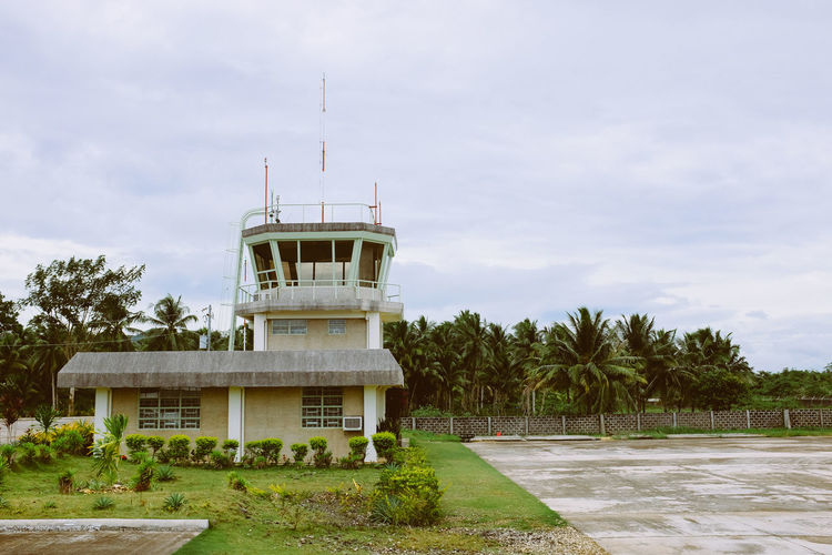 Airport tower with jungle in the background Airport Airport Runway Architecture Building Exterior Built Structure Cloud - Sky Day Grass Nature No People Outdoors Palm Tree Sky Tower Transportation Tree Vacations Water
