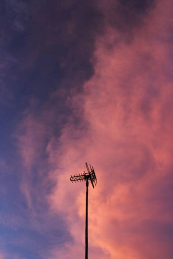 Low angle view of silhouette telephone pole against sky during sunset