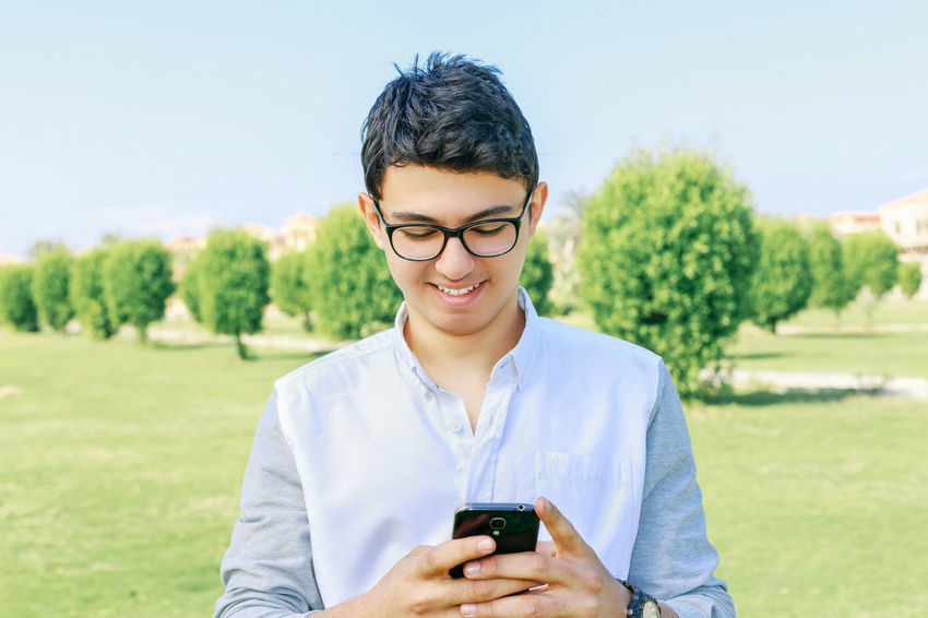 Communication Connection Eyeglasses  Front View Holding Leisure Activity Lifestyles Man Mobile Mobile Phone Nature One Person Outdoors Park - Man Made Space Phone Portrait Smart Phone Smile Technology Text Messaging Tree Using Phone Wireless Technology Young Young Adult
