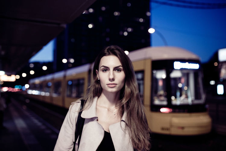 Portrait of young woman standing against train at railroad station