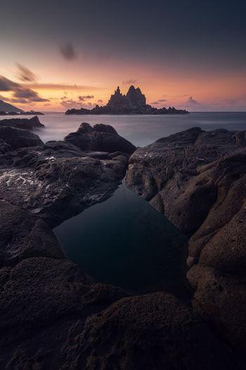 Rocks on beach against sky during sunrise