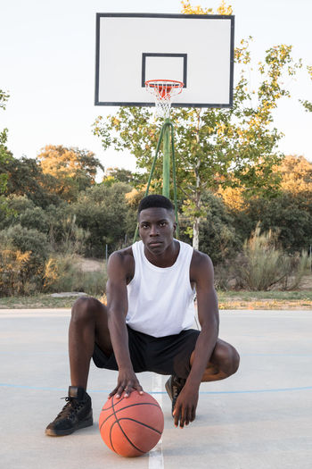 Young Man Standing With Ball On Basketball Court