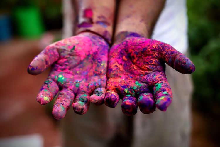 Cropped hands with multi colored powder paint