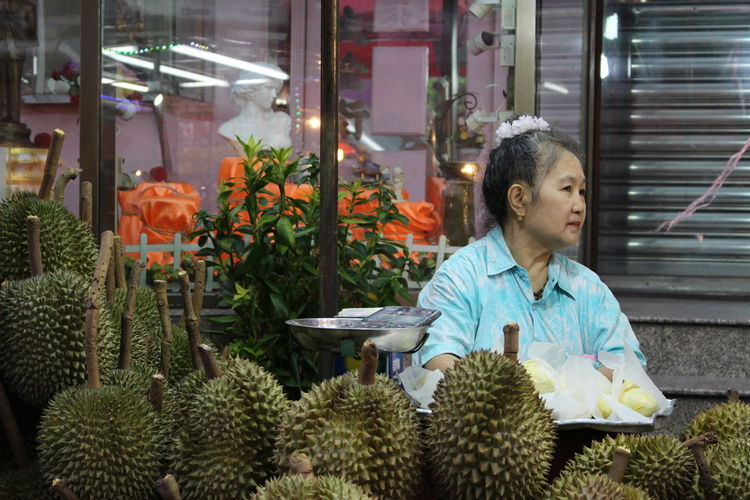 Woman selling durian fruit at market stall