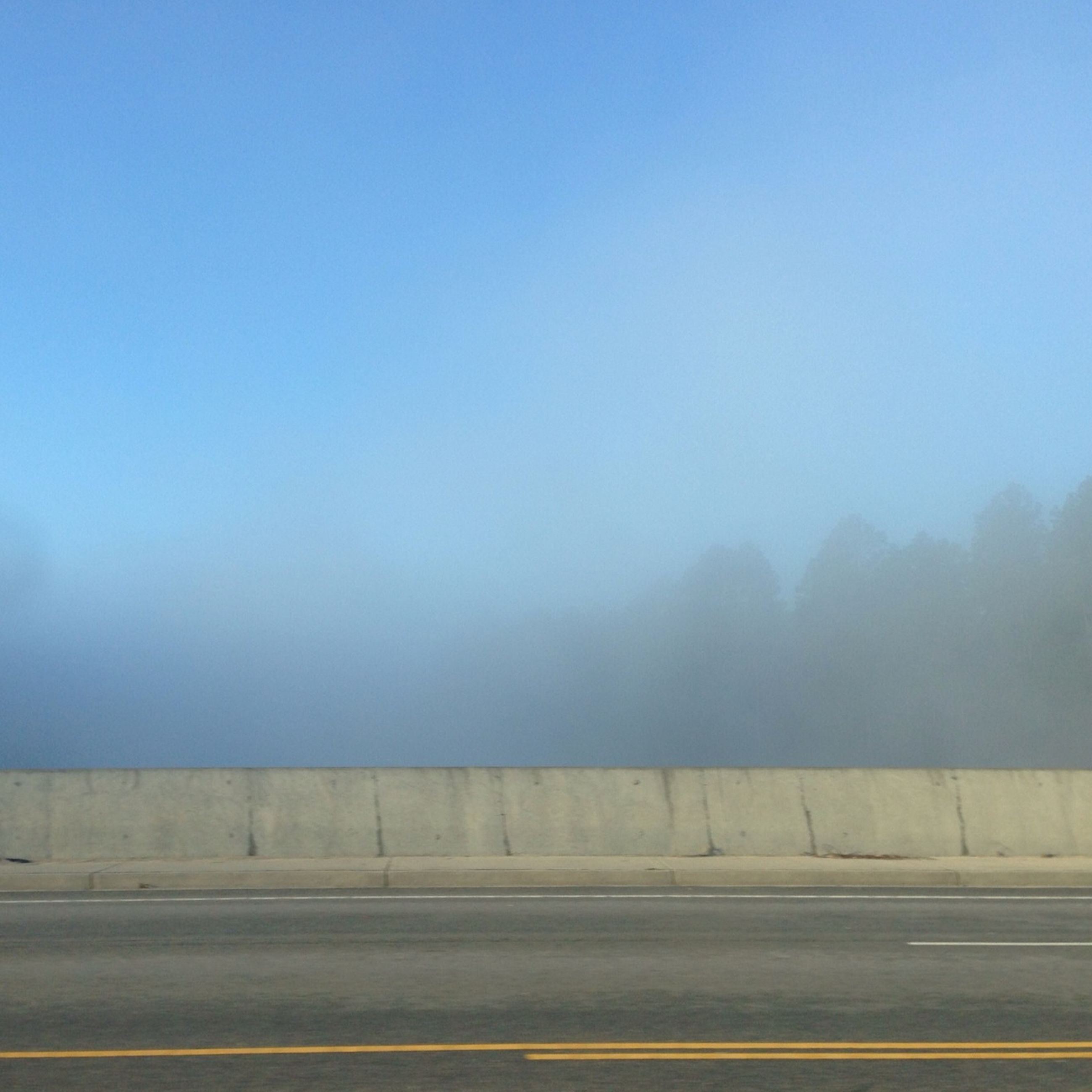 copy space, clear sky, foggy, road, sky, transportation, tranquility, tranquil scene, weather, landscape, nature, blue, scenics, built structure, beauty in nature, day, outdoors, no people, architecture
