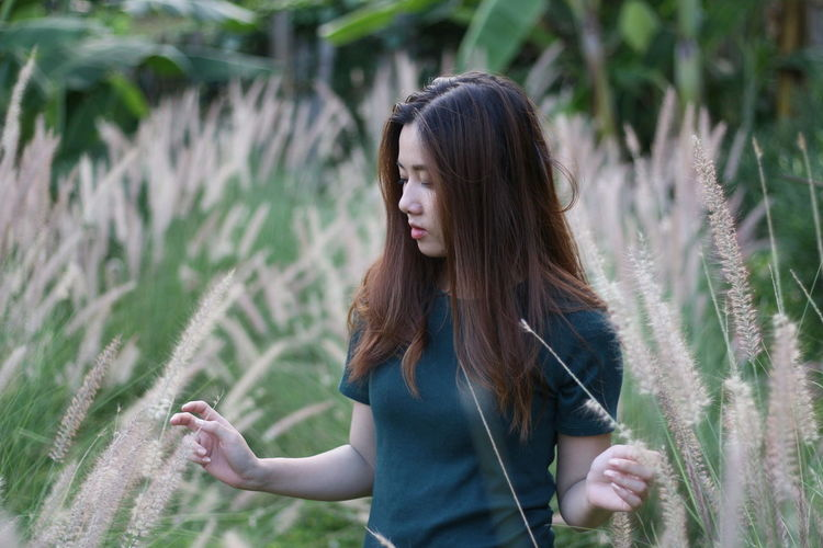 Young woman standing amidst plants on field