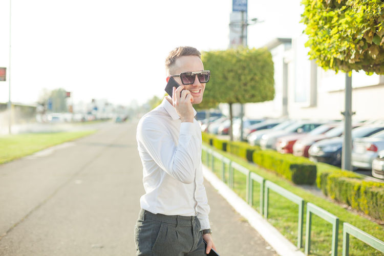 Young man talking on smart phone while standing in city