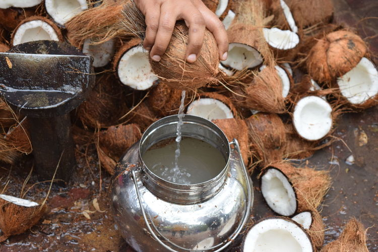 Cropped hand of man pouring coconut water in container