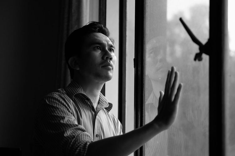 A man standing Real People One Person Window Indoors  Lifestyles Young Adult Headshot Day Young Women Close-up People Monochrome Black And White Blackandwhite Adult Hand Touching Self Portrait Selfportrait Portrait Front View Standing Looking Through Window Indoors  Resist TCPM The Portraitist - 2017 EyeEm Awards