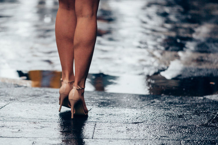 Low section of woman wearing high heals standing on footpath by lake