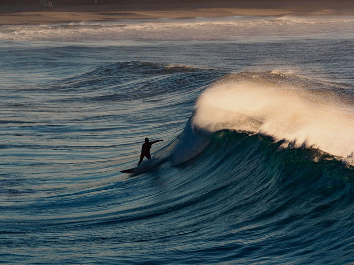 Person surfing on waves at sea