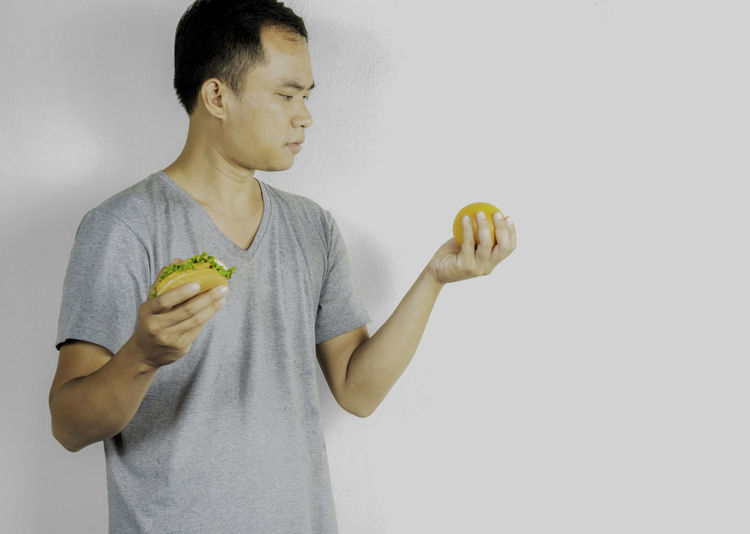 Man looking at orange while holding burger while standing against white background