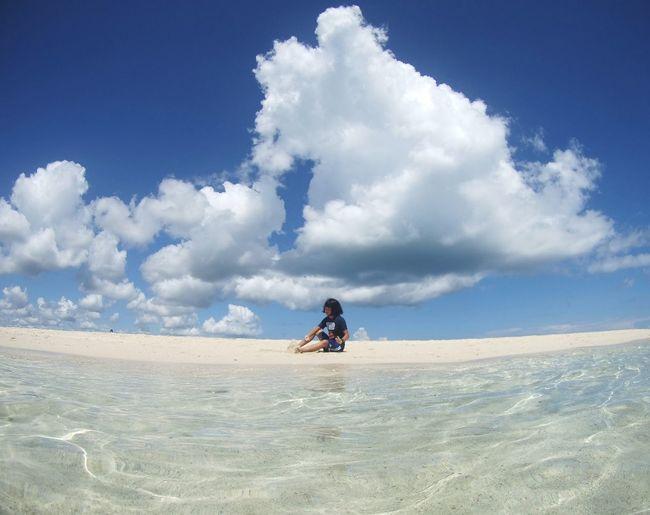 Woman sitting on sand dune in desert against sky
