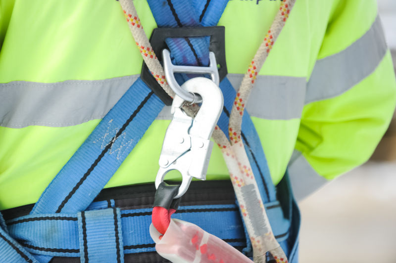 hook of the safety carabiner attached to the safety belt is worn on the worker. Real People One Person Day Human Body Part Metal Human Hand Close-up Hand Connection Holding Safety Midsection High Angle View Green Color Outdoors Protection Working Security Carabiner Hook