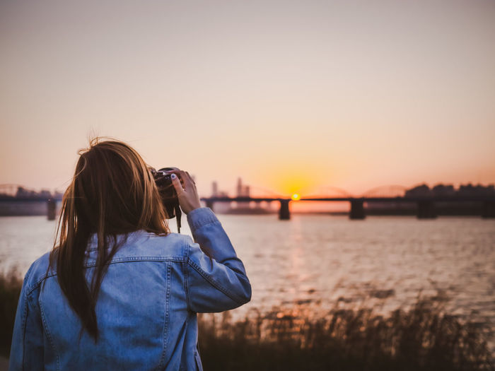 Young woman photographing against sky during sunset
