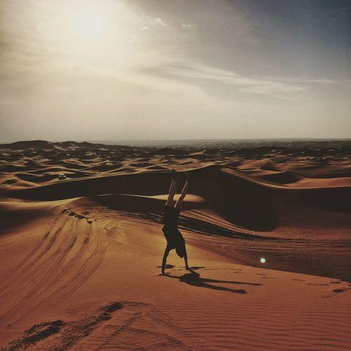 Man Doing Handstand At Desert Against Sky