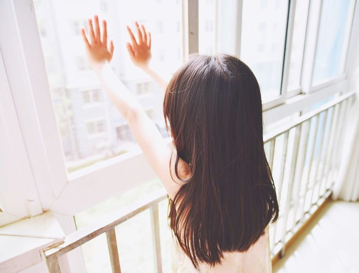 High Angle View Of Girl Touching Glass Window