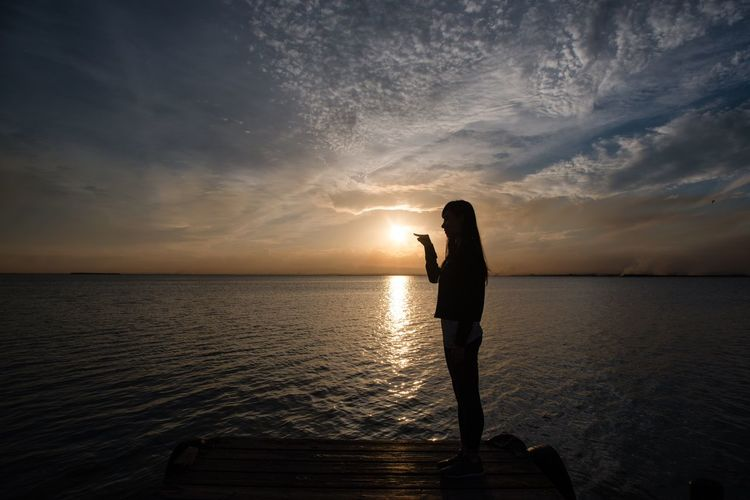 Water Sea Silhouette Sunset Standing Horizon Over Water Tranquility Sky Tranquil Scene Scenics Reflection Cloud - Sky Sun Beauty In Nature Person Nature Cloud Vacations Outdoors Non-urban Scene