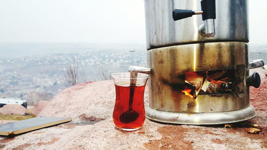 Turkish in tea glass by camping stove on rock