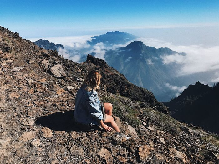 Man sitting on rock against mountain range