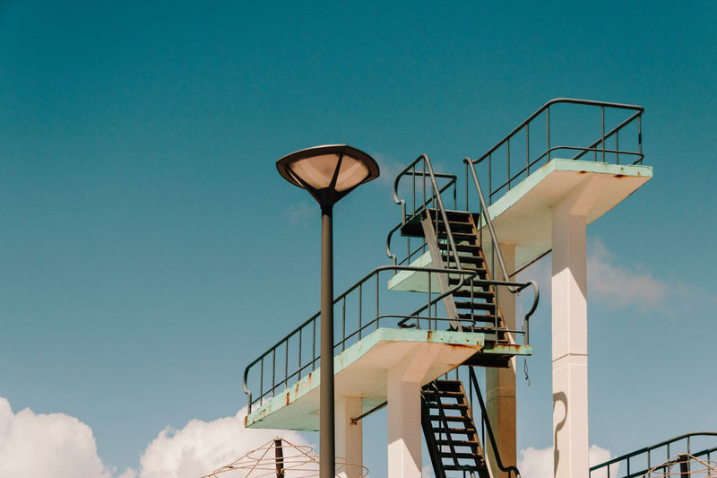 Low angle view of lamp post and staircase against sky