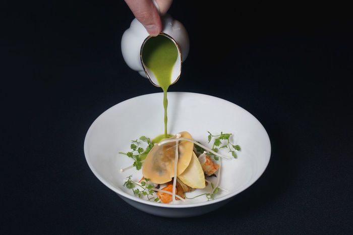 Ravioli with porcini and king prawns with green curry. Curry Food Art Green Porcini Ravioli Black Background Close-up Fine Dining Food Freshness Healthy Eating Holding King Prawns Plating Plating Food Soup Studio Shot Table