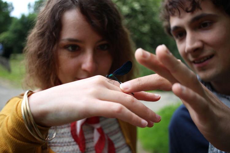Close-up of man and woman looking at dragonfly