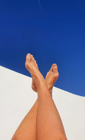 Low section of woman legs against clear blue sky