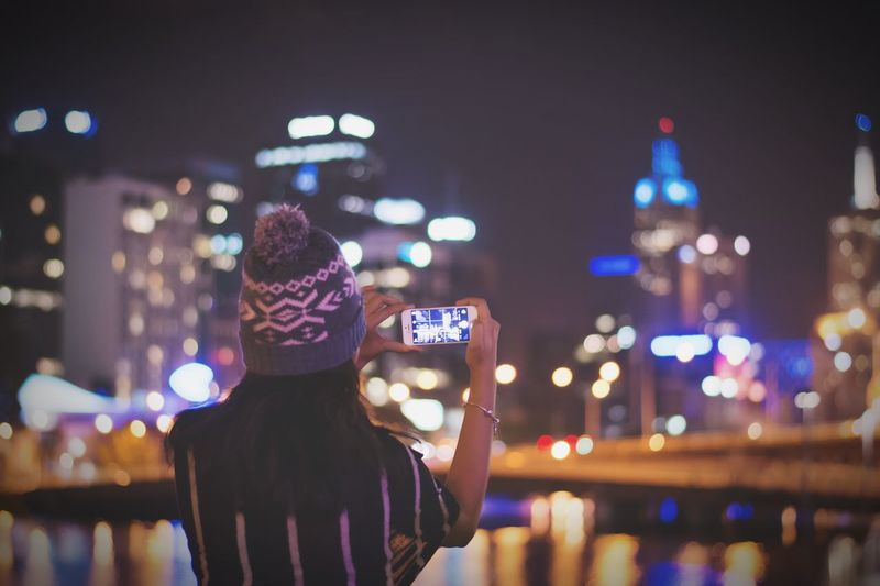 Rear View Of Woman Photographing Illuminated City Through Smart Phone At Night