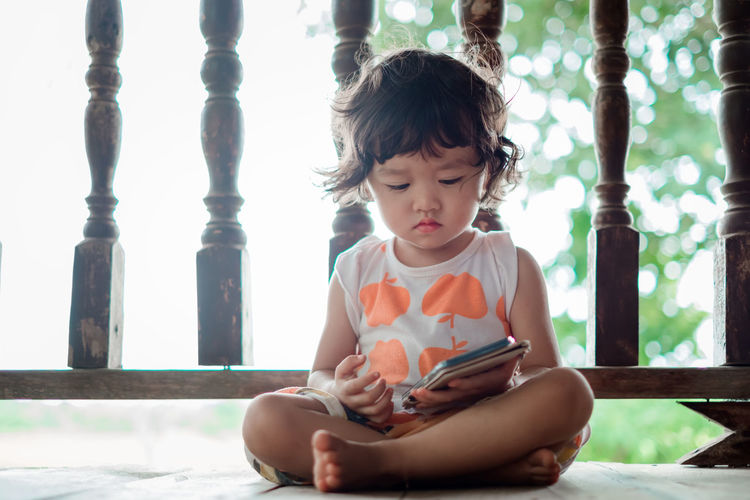 Cute girl watching video over smart phone while sitting against railing