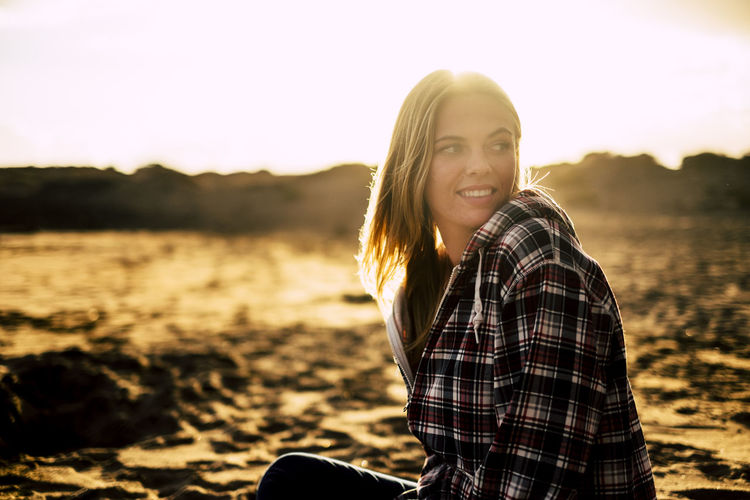Smiling young woman sitting on sand against sky during sunset