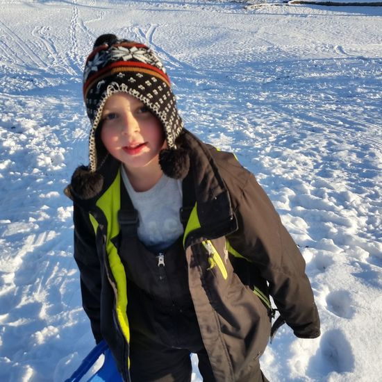 Portrait Of Boy Wearing Knit Hat Standing On Snow Covered Field