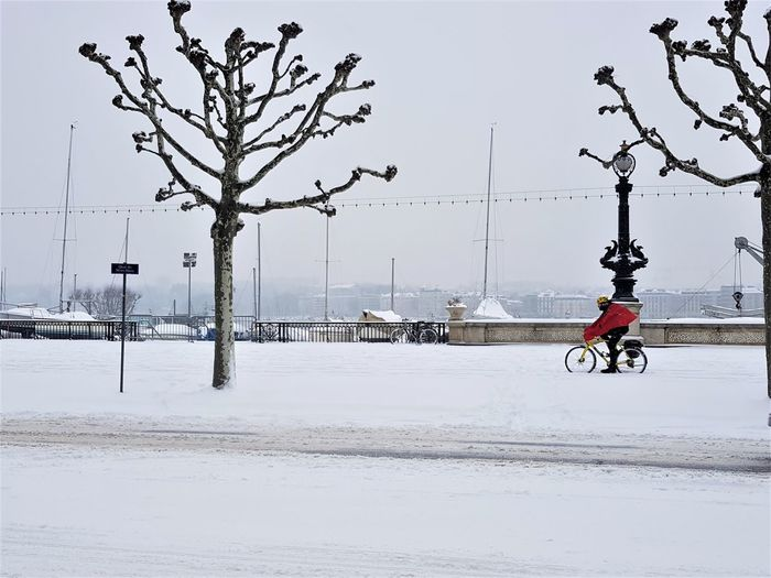 Man riding bicycle on street in winter