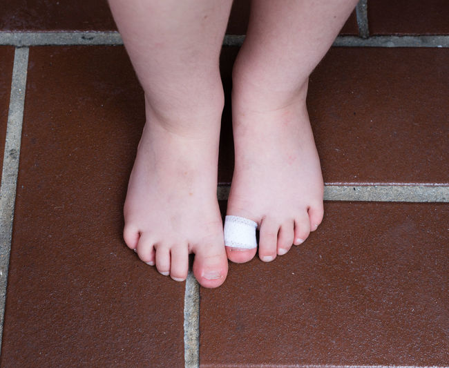 Low Section Of Child With Bandage Standing On Floor