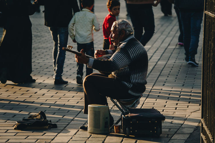 A man plays a traditional instrument in the streets of Istanbul amongst a large crowd. - IG: @LostBoyMemoirs (All photos taken on Sony A6300 and edited in Lightroom). Istanbul Turkey Turkish EyeEm Best Shots The Week on EyeEm Streetwise Photography Streetphotography Street Photography People People Watching people and places Travel Group Of People Real People Musical Instrument Performance Musician Lifestyles Street Musician Busker Analogue Sound The Art Of Street Photography