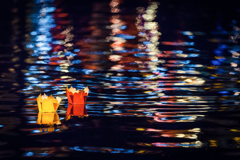 Paper boats in lake at night