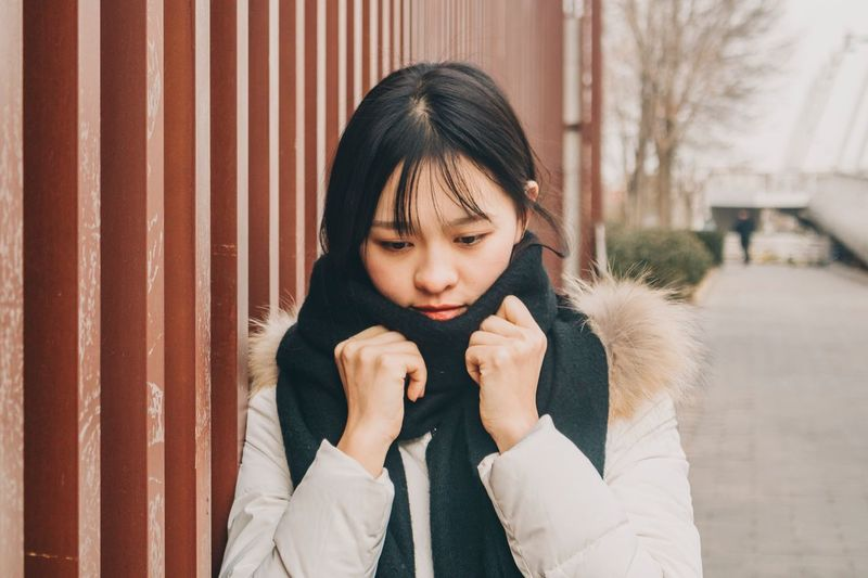 Young woman wearing warm clothing in city during winter