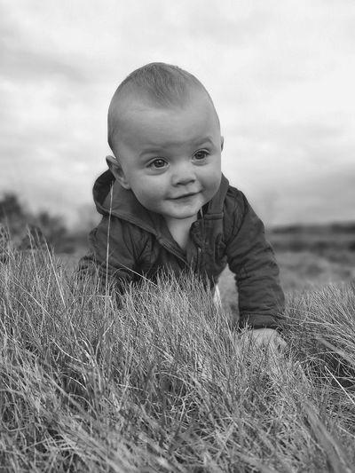 Portrait of boy on field against sky