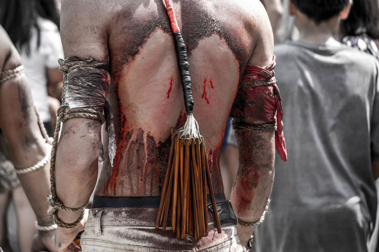 Rear View Of Shirtless Man With Wounds Standing Outdoors